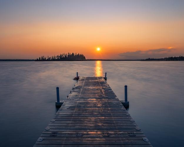 Muelle de madera vacía en un lago durante una impresionante puesta de sol, un fondo fresco