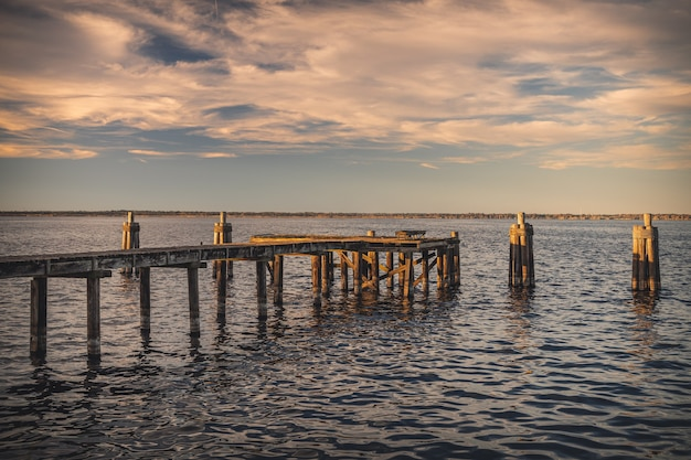 Muelle de madera vieja en el mar bajo la luz del sol durante la puesta de sol