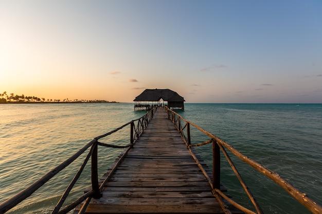 Muelle en el mar durante una hermosa puesta de sol en zanzíbar, áfrica oriental