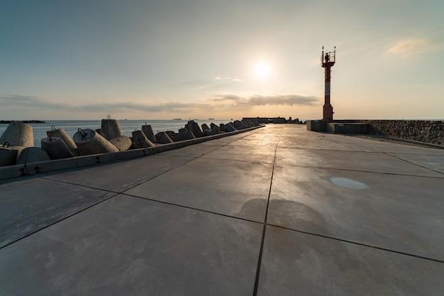 Muelle norte con rompeolas, paisaje marino al atardecer. faro moderno en la luz del sol.