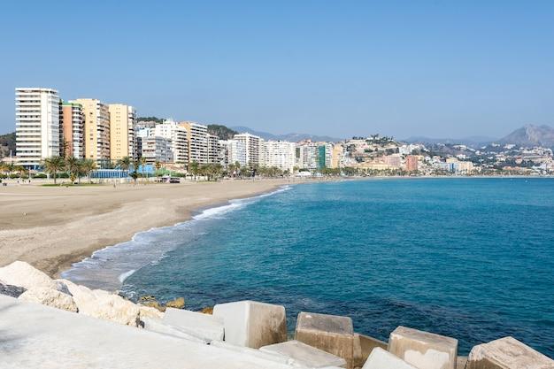 Muelle del puerto de málaga con la playa al fondo.