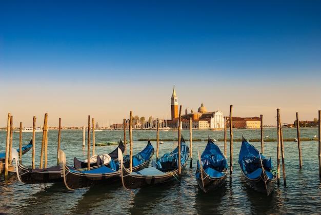 Muelle de venecia con icónicas góndolas como primer plano y la capilla diseñada por andrea palladio.