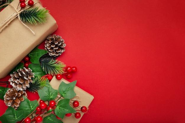 Muérdago, piñas y regalos de navidad en mesa roja