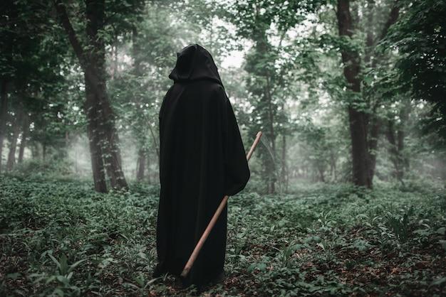 Muerte con una guadaña en el bosque oscuro y brumoso