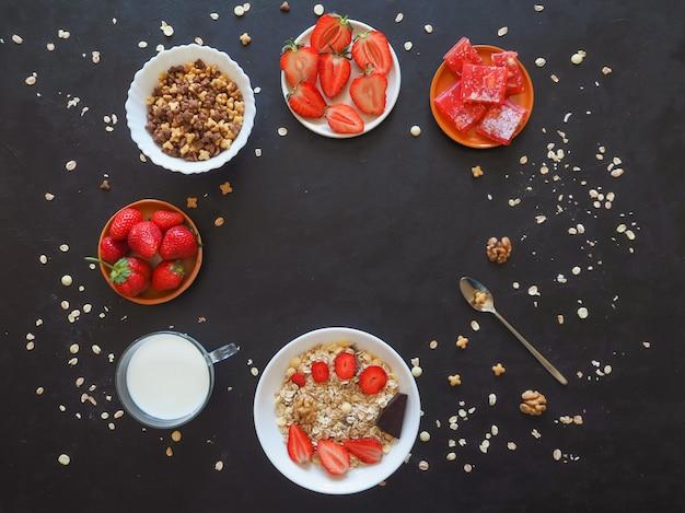 Muesli con fresas en una mesa negra. desayuno tradicional europeo con muesli.