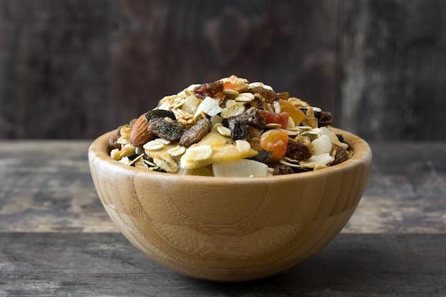 Muesli y frutos secos en un tazón de madera sobre la mesa de madera.