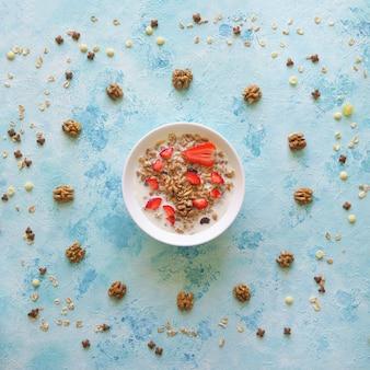 Muesli en un recipiente con fresas en una mesa azul. granola con fresas.