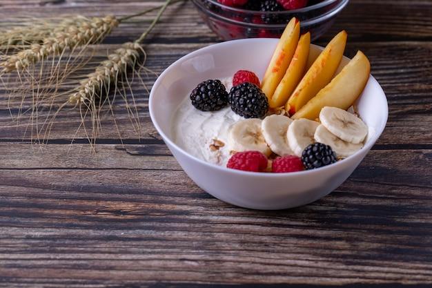 Muesli con yogurt y fruta sobre una mesa de madera oscura.