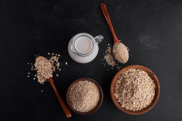 Mueslies en tazas de madera con un tarro de leche, vista superior.