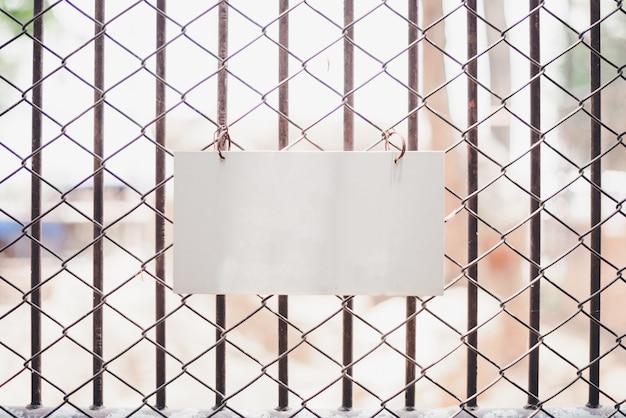 Muestra en blanco colgando en frente de la cerca en el zoológico