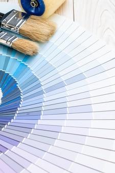 Muestra el catálogo de colores pantone o libro de muestras de color con rodillo de pintura
