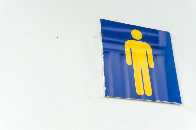 Muestra masculina del retrete en la pared blanca.