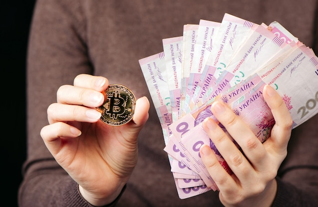 Muestra una moneda de oro bitcoin: un símbolo de criptomoneda, nuevo dinero virtual y una pila de dinero hryvnia ucraniano, enfoque selectivo, tonificado.