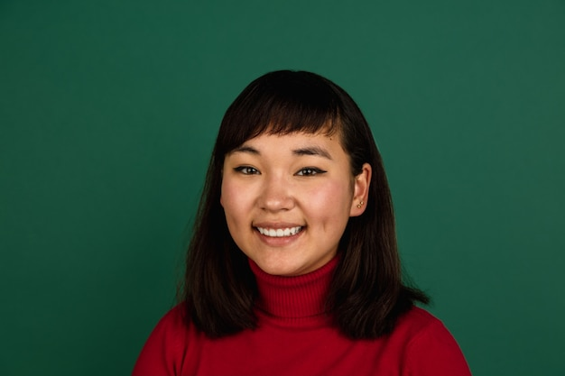 Muestra la pantalla del teléfono en blanco. retrato de mujer hermosa joven de asia oriental sobre fondo verde con copyspace.