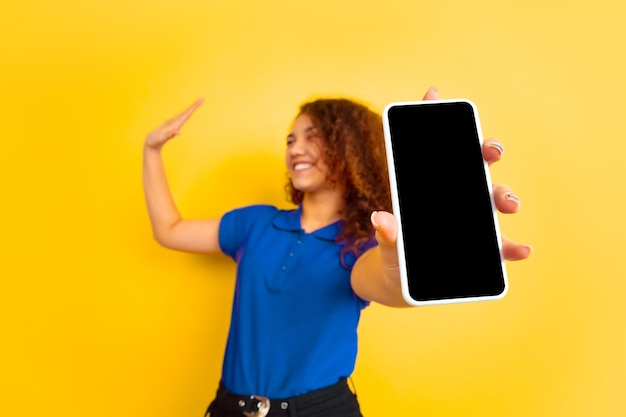 Muestra la pantalla del teléfono. retrato de la muchacha del adolescente caucásico en la pared amarilla. modelo rizado femenino hermoso en camisa. concepto de emociones humanas, expresión facial, ventas, publicidad, educación. copyspace.