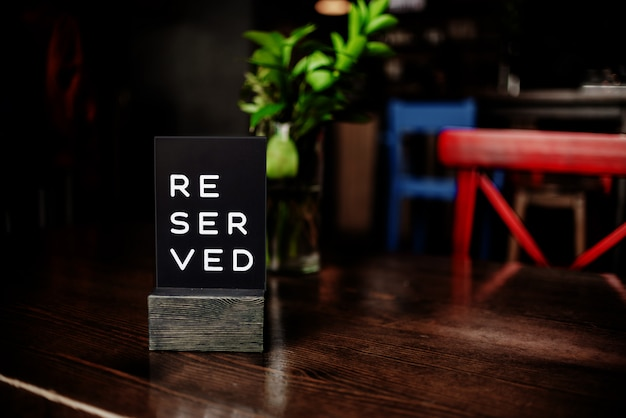 Muestra reservada en una mesa en restaurante. silla y florero rojos. vista horizontal de varios objetos.