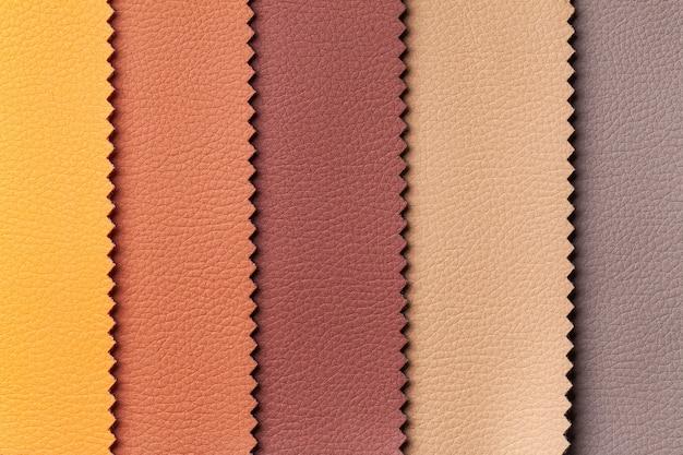 Muestra de textiles de cuero marrón y rojo, fondo. catálogo y muestrario de tejidos de interior para mobiliario.