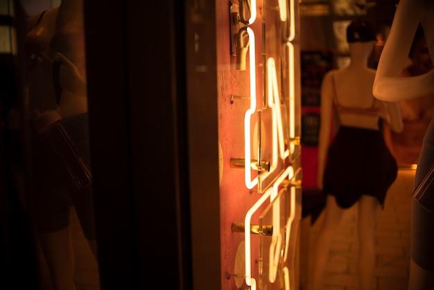 Muestra de la tienda en luces de neón con maniquí