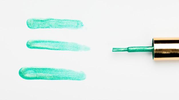 Muestra de trazo de esmalte de uñas verde cerca de pincel sobre fondo