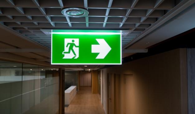 La muestra verde de la salida de incendios cuelga en el techo en la oficina.