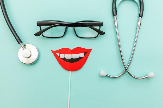 Muestra de los vidrios del estetoscopio del equipo de la medicina de los dientes de la sonrisa aislados en azul en colores pastel de moda
