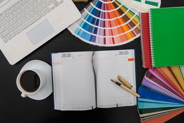 Muestrario de colores con portátil y diario en la oficina