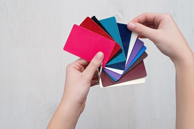 Muestras de moda coloridas hechas de cuero genuino en manos del diseñador, tiendas modernas, concepto de industria. catálogo de paletas con muestras de cuero de color.