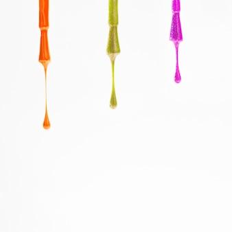 Muestras de varios colores de esmalte de uñas en los pinceles sobre fondo blanco