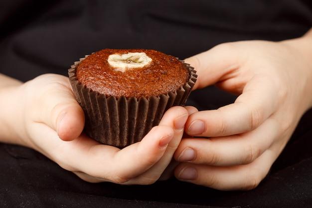 Muffin casero de chocolate y plátano en manos de niños