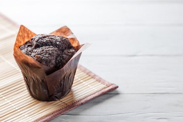Muffin de chocolate en mesa de madera con espacio de copia