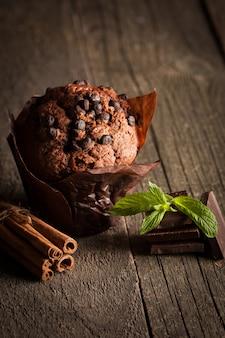 Muffin de chocolate negro cocido con menta en una mesa de madera con canela, anís, chocolate.