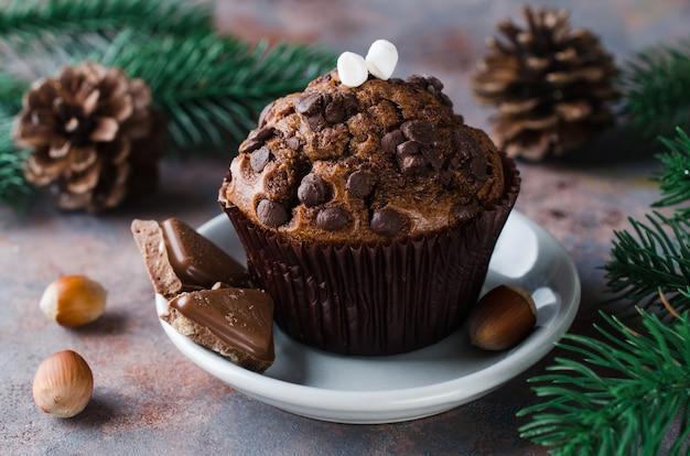 Muffin de chocolate y ramas de abeto. tiempo de navidad.