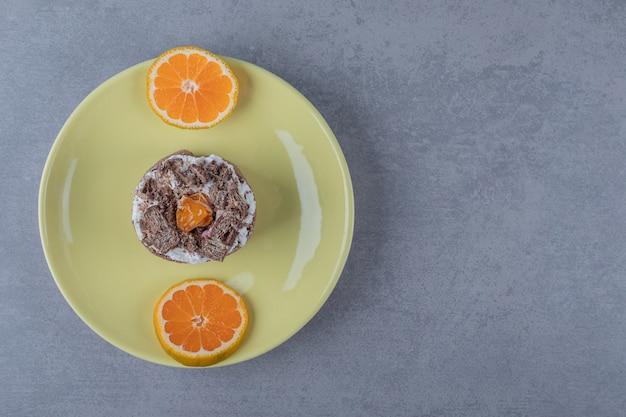 Muffin cremoso fresco con rodajas de naranja sobre placa amarilla
