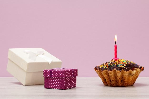 Muffin de cumpleaños sabroso con glaseado de chocolate y caramelo, decorado con velas festivas ardientes y cajas de regalo sobre fondo violeta. feliz cumpleaños concepto mínimo.