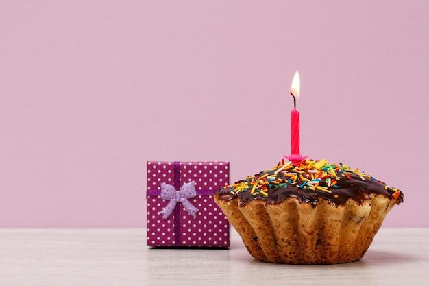 Muffin de cumpleaños sabroso con glaseado de chocolate y caramelo, decorado con velas festivas encendidas y caja de regalo sobre fondo violeta. feliz cumpleaños concepto mínimo.