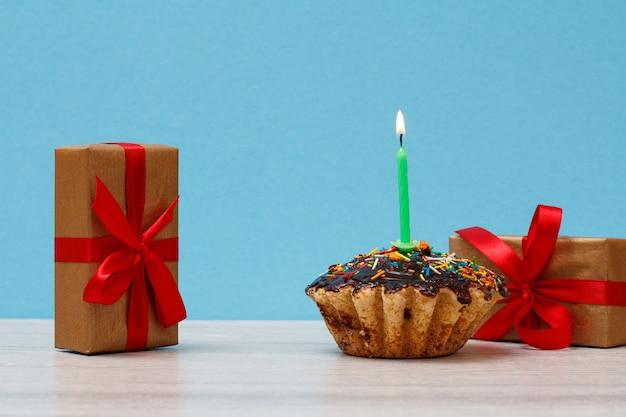Muffin de cumpleaños sabroso con glaseado de chocolate y caramelo, decorado con velas festivas encendidas y cajas de regalo sobre fondo azul. feliz cumpleaños concepto mínimo.