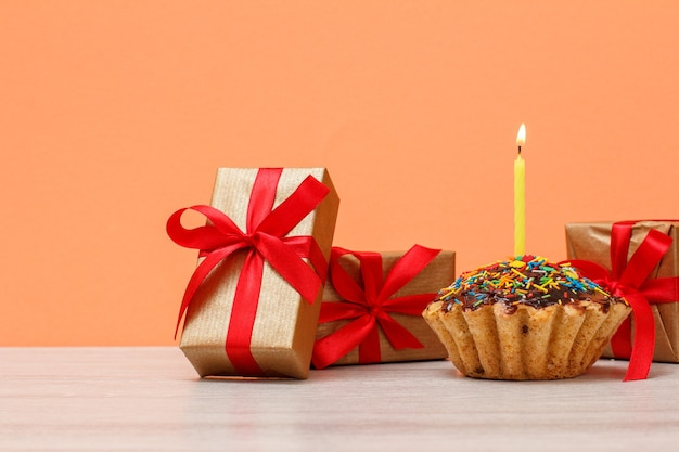 Muffin de cumpleaños sabroso con glaseado de chocolate y caramelo, decorado con velas festivas encendidas y cajas de regalo sobre fondo naranja. concepto de feliz cumpleaños.