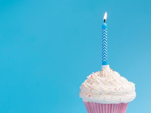 Muffin de cumpleaños sobre fondo azul.