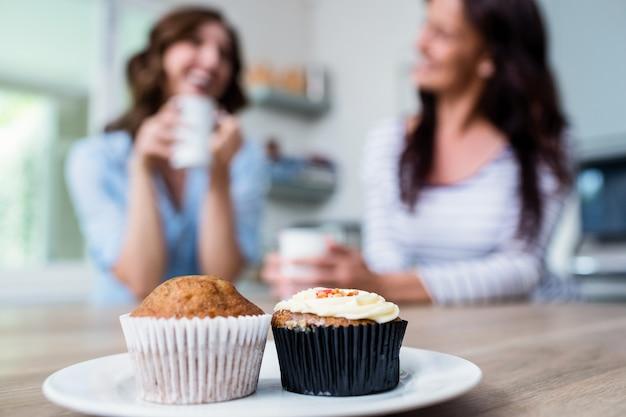 Muffin y cupcake servido en la mesa con amigos sentados en segundo plano.