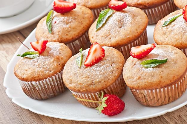 Muffin de fresa en un plato blanco con una fresa fresca