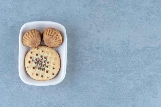 Muffin fresco casero y galleta en cuenco de cerámica blanca.