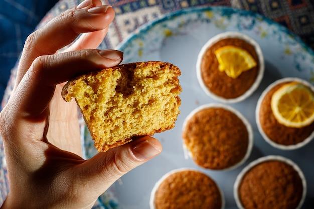 Muffin fresco en la mano de una mujer. textura de primer plano de la masa.
