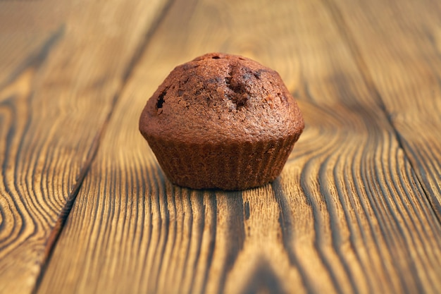 Un muffin de masa de chocolate negro en el fondo de una vieja mesa de madera.