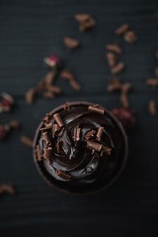 Muffin o cupcake con crema de chocolate en forma de mesa negra. vista superior de flatlay.