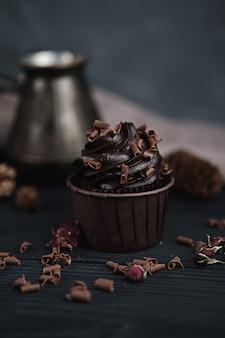 Muffin o cupcake con crema de chocolate en forma de mesa negra.