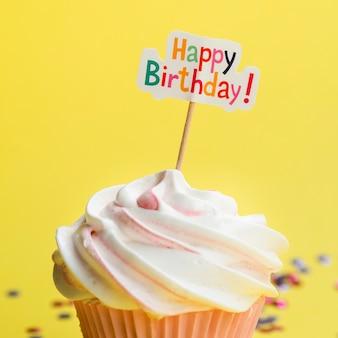 Muffin sabroso con cartel de feliz cumpleaños