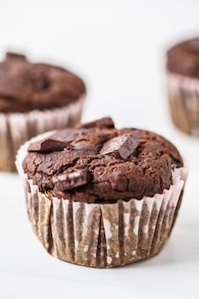 Muffin vegano de chocolate en una taza de papel en blanco