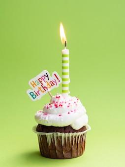 Muffin con vela y cartel de feliz cumpleaños