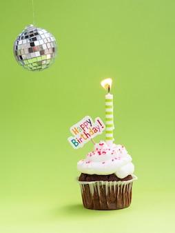 Muffin con vela disco globe y cartel de feliz cumpleaños