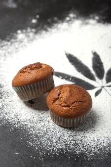Muffins con cannabis en la mesa, fondo oscuro. concepto de comida cdb